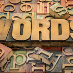 words text in wood type against background of letterpress printing blocks